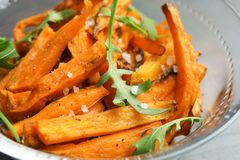 Glass bowl with baked sweet potato slices and arugula. Closeup royalty free stock photo