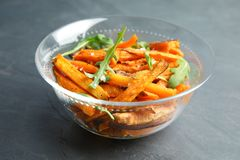 Glass bowl with baked sweet potato slices and arugula. On grey background royalty free stock photos