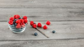Glass bowl with blueberries and raspberries on top, with spoon a. Nd some spilled berries on the side placed on gray wood desk stock photos