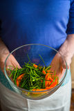 Glass bowl with carrots and spring onion slices in the hands. Vertical Stock Photos