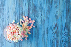 Glass bowl of colored marshmallows, on blue background Royalty Free Stock Images