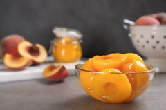 Glass bowl with conserved peach halves on grey table. Space for text royalty free stock images