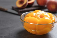 Glass bowl with conserved peach halves on grey table. Space for text royalty free stock photography
