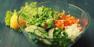 Glass bowl with cut vegetables for a salad. Royalty Free Stock Images