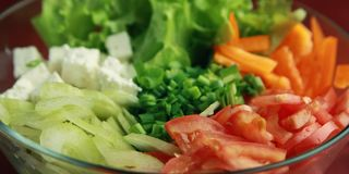 Glass bowl with cutted vegetables. Close up. Glass bowl with cutted vegetables for a salad. Close up. Tomatoes, celery, bell pepper, leafy greens and cottage Stock Photo
