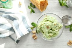 Glass bowl with delicious pistachio ice cream. On white wooden table royalty free stock image