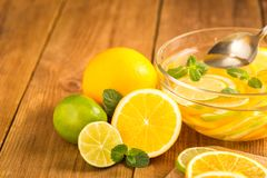 Glass bowl with detox water with slices of orange and lime. Royalty Free Stock Images
