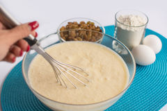 Glass bowl with dough and whisk in a female hand, Royalty Free Stock Image