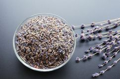 Dry lavender tea. Glass bowl with dried lavender tea and lavender flowers bouquet over grey board background stock photos