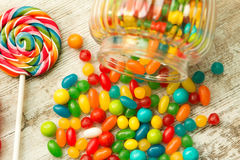 Glass bowl fallen with  jelly beans and a lollipop Stock Photo