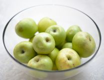 Glass bowl filled with green apples Stock Images