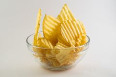 Glass bowl filled with ribbed fries. Glass bowl filled ribbed fries potatoes unhealthy snack fat yummy salty crunchy chips slices stock images