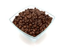 Glass bowl filled to the brim with coffee beans. Glass bowl filled to the brim with dark roasted coffee beans, on a white background royalty free stock photography