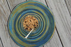 Glass bowl of flavorful granola on colorful round placemat. Glass bowl with healthy,flavorful granola,nuts and berries on colorful placemat and gray board Stock Image