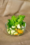 Glass bowl with fresh green salad pained fresh fruit Stock Photography