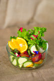 Glass bowl with fresh green salad pained fresh fruit Royalty Free Stock Images