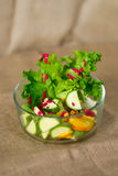 Glass bowl with fresh green salad pained fresh fruit Stock Photos