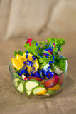Glass bowl with fresh green salad pained fresh fruit Royalty Free Stock Photos
