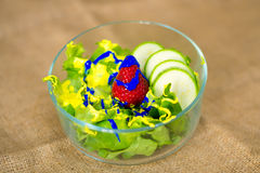 Glass bowl with fresh green salad pained fresh fruit. Glass bowl containing green salad, strawberry, courgettes and blue acrylic paint Stock Images