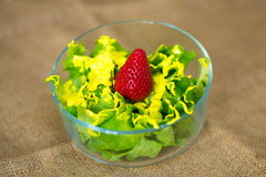 Glass bowl with fresh green salad pained fresh fruit. Glass bowl containing green salad, strawberry and yellow acrylic paint Royalty Free Stock Images