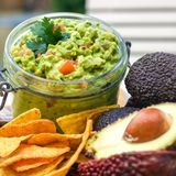 Fresh guacamole. Glass bowl of fresh home made mexican guacamole with tortilla chips and avocado's stock photography