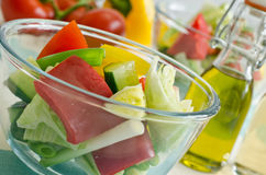 Glass bowl of fresh salad with oil Royalty Free Stock Photo