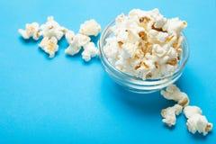 Glass bowl of freshly popped popcorn isolated stock photography