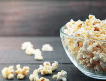Glass bowl with freshly popped popcorn with salt on dark wooden Royalty Free Stock Photo