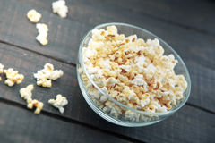 Glass bowl with freshly popped popcorn with salt on dark wooden Royalty Free Stock Image