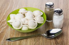 Glass bowl with frozen dumplings, salt, pepper and spoon. On wooden table Royalty Free Stock Photography