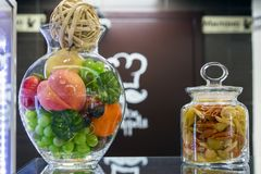 A glass bowl of fruit and a jar of pasta in the interior of the cafe stock images