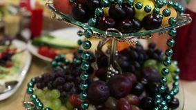 Glass bowl with fruits and beads. Fresh fruit wrapped in beads with garlands to decorate wedding table stock video