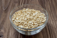Glass bowl full of oats seed on wooden background Royalty Free Stock Images