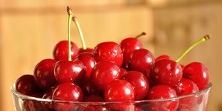 Glass bowl full of red ripe cherries Royalty Free Stock Photography