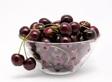 A glass bowl full with sweet cherries isolated Royalty Free Stock Images