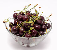 A glass bowl full with sweet cherries isolated Royalty Free Stock Photo