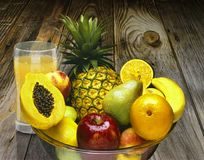 GLASS BOWL FULL OF VARIOUS FRUITS AND GLASS OF JUICE BEHIND royalty free stock images