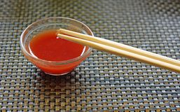 Glass bowl with hot sauce with chopsticks Chinese restaurant Royalty Free Stock Photography