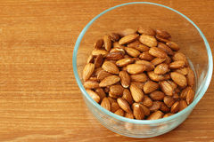 Glass Bowl of Maple Glazed Almonds. Baked maple syrup coated almonds with salt in a round glass bowl on a wooden table. A healthy and sweet snack of maple syrup Royalty Free Stock Image
