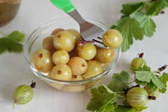 Glass bowl with marinated green gooseberries Stock Images
