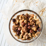 Glass bowl of mixed nuts on parchment paper and cooling rack. On white Stock Images