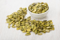 Glass bowl with peeled pumpkin seeds and scattered seeds stock photos