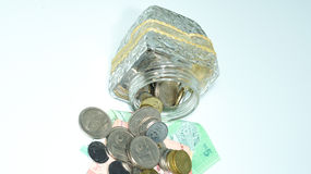 Glass bowl with piles of coins and Malaysia bank notes. Royalty Free Stock Images