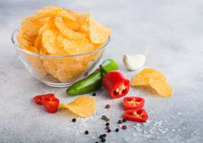 Glass bowl plate with potato crisps chips with chilli pepper on light table background. Red and green chilli pepper with garlic. Glass bowl plate with potato royalty free stock photo