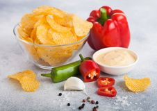 Glass bowl plate with potato crisps chips with chilli pepper on light table background. Red and green chilli pepper with garlic. Glass bowl plate with potato royalty free stock photos