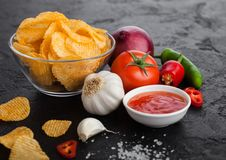 Glass bowl plate with potato crisps chips with paprika and chilli peppers on black stone table background. Red onion with tomato. Glass bowl plate with potato stock photos