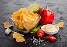 Glass bowl plate with potato crisps chips with paprika and chilli peppers on black stone table background. Red paprika pepper with. Glass bowl plate with potato stock photos