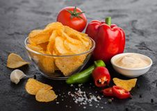 Glass bowl plate with potato crisps chips with paprika and chilli peppers on black stone table background. Red paprika pepper with. Glass bowl plate with potato royalty free stock image