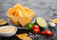 Glass bowl plate with potato crisps chips with paprika flavour on black stone table background. Red and green chilli peppers with. Glass bowl plate with potato royalty free stock image