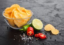 Glass bowl plate with potato crisps chips with paprika flavour on black stone table background. Red and green chilli peppers with. Glass bowl plate with potato stock images